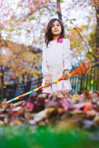 young girl holding a rake in the garden