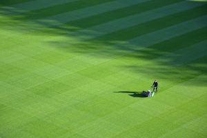 man mowing a sports ground